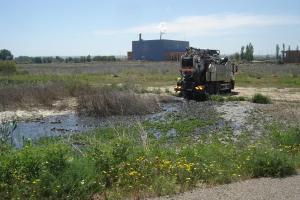 Camión de FCC echando su carga cerca del Río Ebro, detrás, la Depuradora